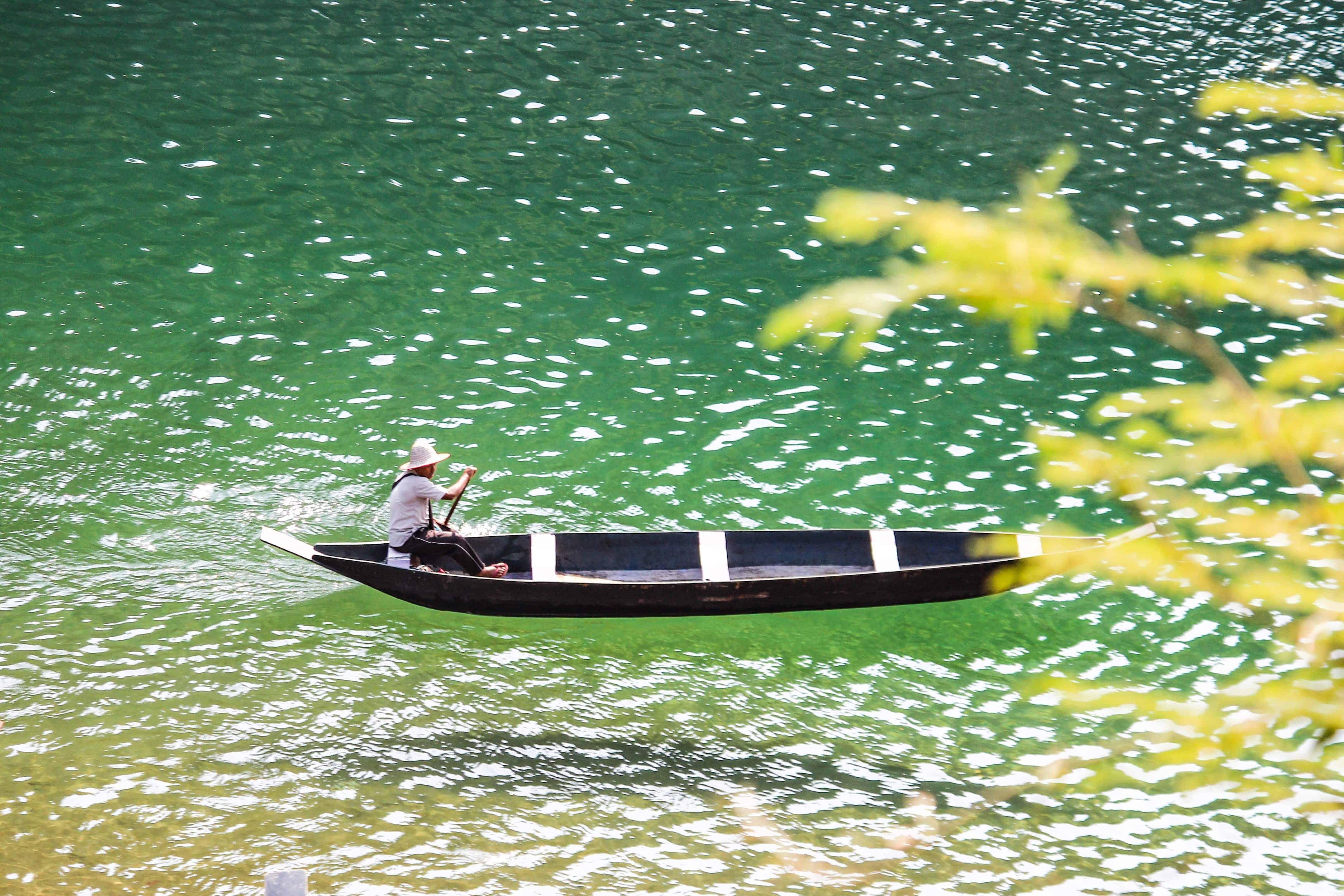 A boatman rowing on Umngot river
